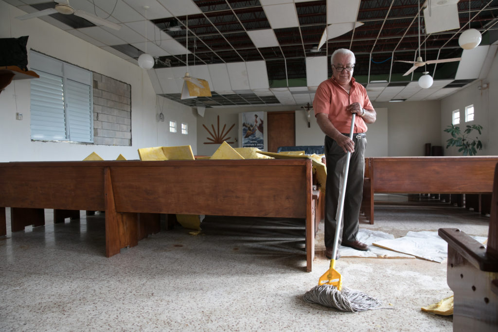 Man cleaning up a destroyed sanctuary after the hurricanes in Puerto Rico