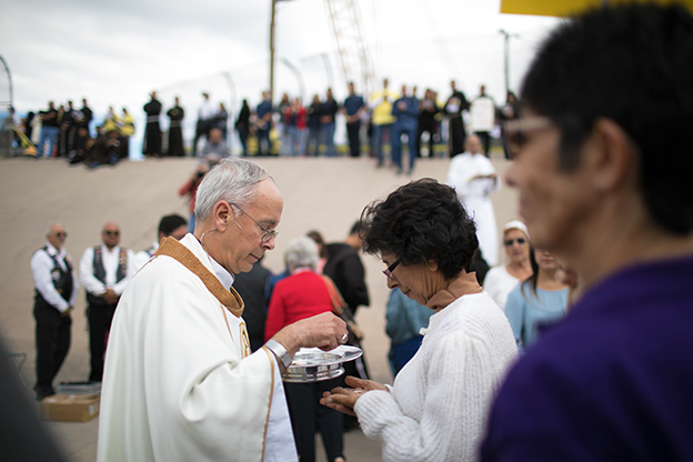 Priest gives communion at Catholic Mass on the border