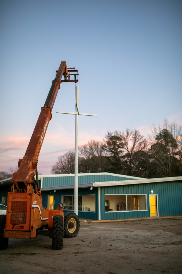A Sky Track holds up a newly installed cross.