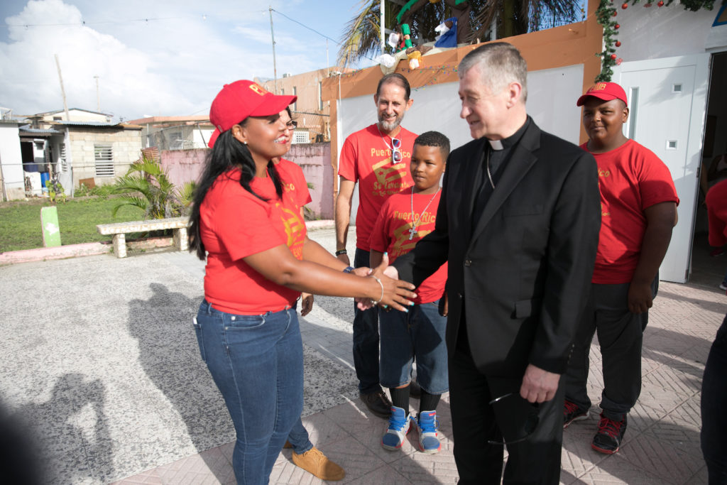 Cardinal Cupich sharing hands with volunteer in Puerto Rico