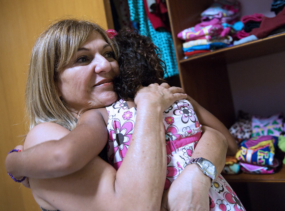 Melva hugs a child