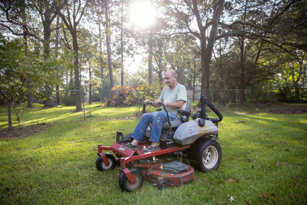 Father Foshage on a riding lawnmower