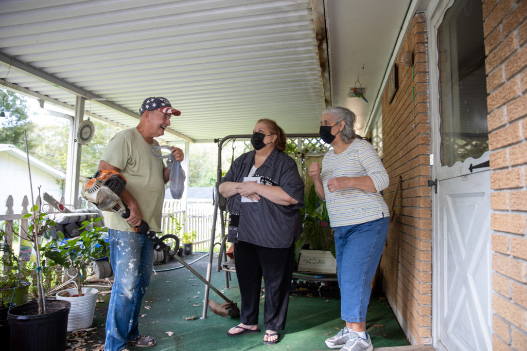 Father Ron Foshage talks with two women on a porch