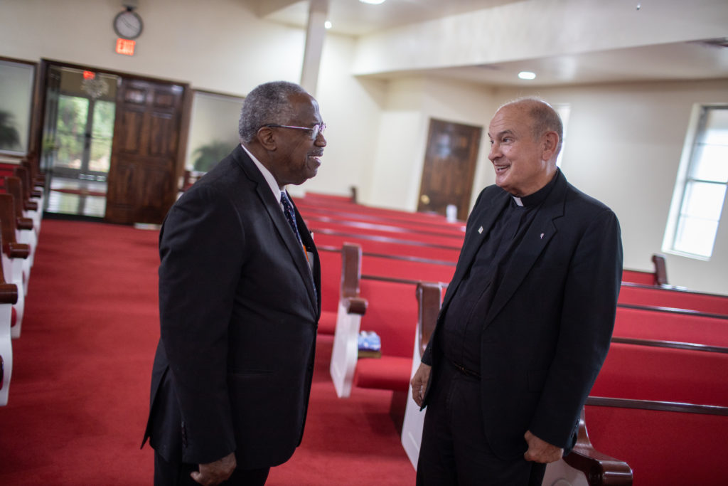 Father Ron Foshage and Pastor Lyons talk in a church