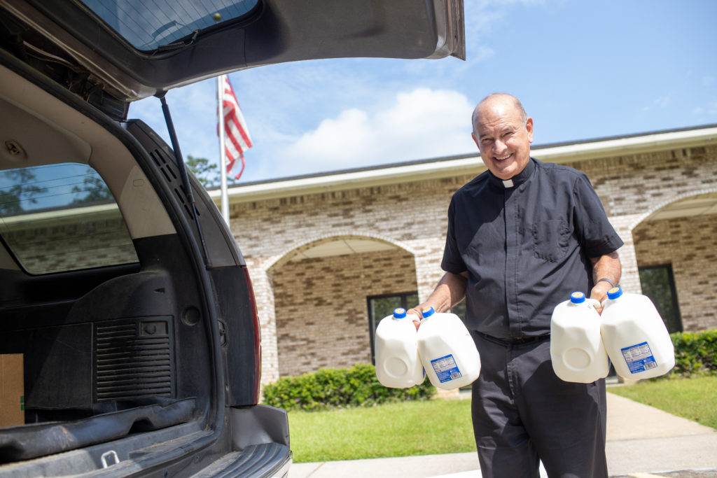 Father Foshage smiling and carrying gallons of milk to place in a car