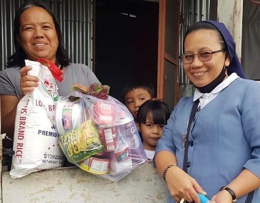 Catholic Sister Saturnina Caccam, SJBP, delivers food to a family struggling amid COVID-19.